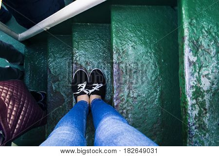 Woman take selfie her feet on green staircases