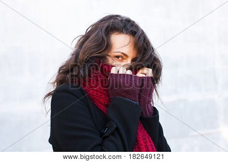Beautiful brunette woman in winter clothes. She is dressed in coat, scarf and gloves.