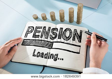 Elevated View Of A Businessperson Drawing Pension Chart On Notebook With Coin Stack On Desk