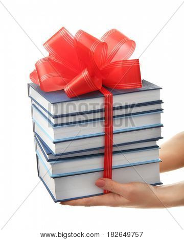 Woman holding stack of books with ribbon as gift on white background