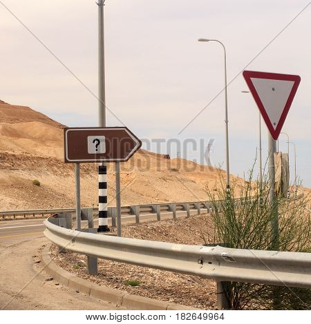 Interrogation mark on road sign and tiangle give way sign.