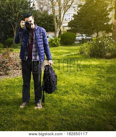 Standing young man taking photography and holds his bag
