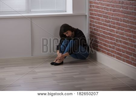 Sad Young Woman Sitting At The Corner Of The Room At Home