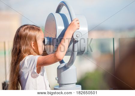 Cute girl looking at coin operated binocular on terrace with beautiful view