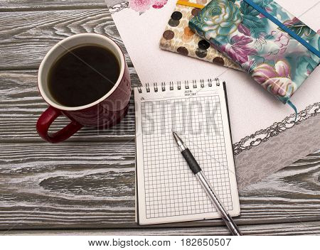 Notebook with coffee on a wooden table. Mock up photo on timbered background.