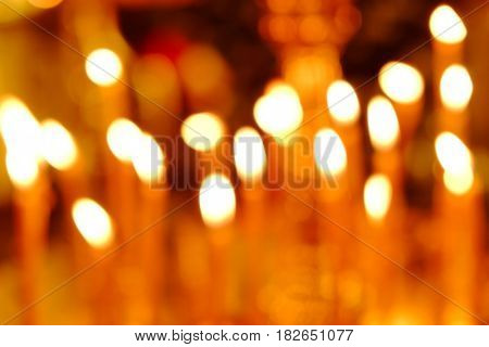 Charming lights of burning candles in church, blurred view