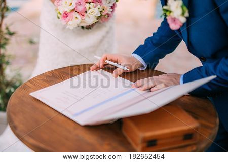 Newlyweds put their signatures in the act of registering a marriage at a wedding ceremony in Montenegro.