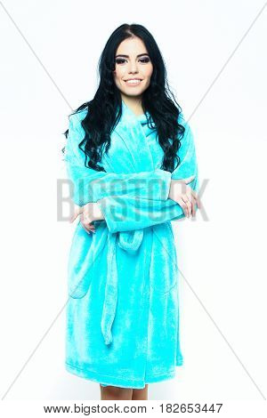pretty cute smiling sexy girl or beautiful happy woman with fashion makeup and curly long hair posing in turquoise velour bathrobe isolated on white background