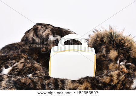 White carton meal box or container on spotted fluffy fur coat background side view
