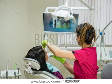 Dentist at work examining woman's teeth in dental clinic with remote camera. Picture of teeth is on the screen. New dental technologies.