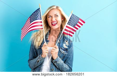 A happy young woman holding American flag