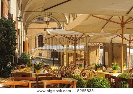 Tables, chairs and umbrellas in Loggia del Vasari ready for diners - Arezzo, Italy