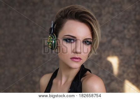 Lovely girl with tanned skin and white hair listening to audio music on headphones. Female beauty portrait of a beautiful makeup. Enjoying good audio. Audio music concept