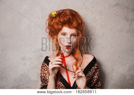 Erotic woman with red hair in leopard print gown with glasses in hand. Red-haired erotic girl with pale skin and blue eyes with a bright unusual appearance with a red ribbon around her neck. French erotic courtesan. Erotic model. Erotic pose