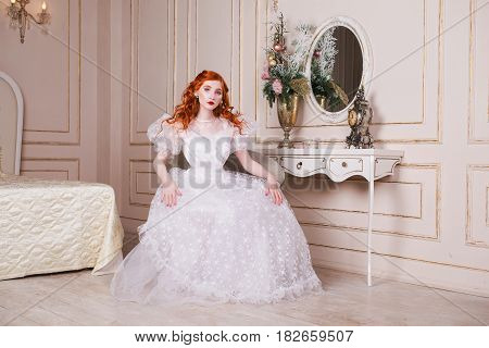 Woman bride with long red curly hair in a white vintage wedding dress with white pearl earrings on her ears. Red-haired bride with pale skin blue eyes a bright unusual appearance in the luxurious bedroom. Nice bride. Bride in wedding dress. Sensual bride.