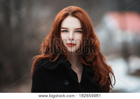 Portrait of a glamorous pretty girl with long red hair in black clothes. A pretty woman in a black coat posing on a background of winter autumn nature. Female street fashion style. Beautiful elegant pretty model