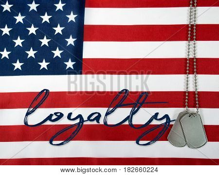 word loyalty and military dog tags on American flag