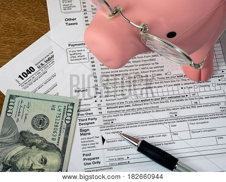 pink pig and hundred dollar bill with pen on 1040 income tax form