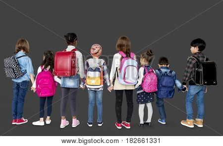 Rear view group of diverse kids standing in a row holdings hands