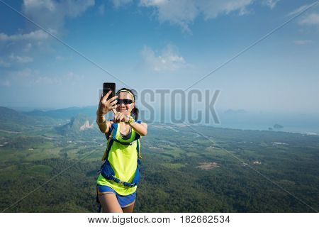 successful woman hiker taking photo with cellphone hiking on mountain peak