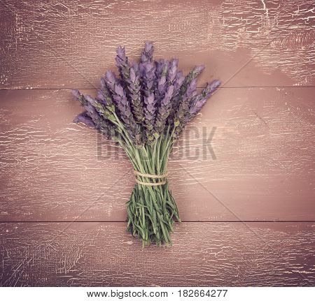 Bundle of lavender flowers on vintage wooden background. Retro style toning