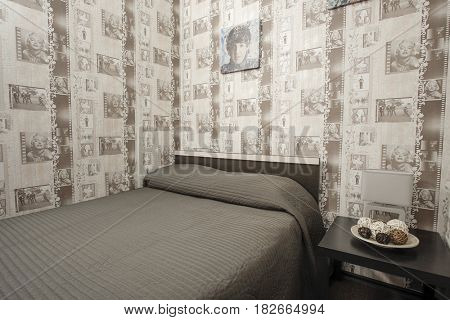 Podolsk, Russia - April, 14. 2017: Interior of a bedroom in a hotel with a wall-paper with the image of different cinema artists