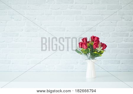 Vase on a wooden table with a white brick wall