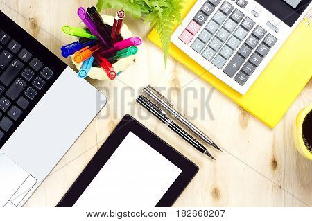 Blank screen tablet and labtop keyboard with financial office supply on wooden background. Woriking table topview in pastel color style.