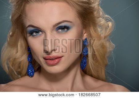 Fashion portrait of young beautiful woman wearing earrings