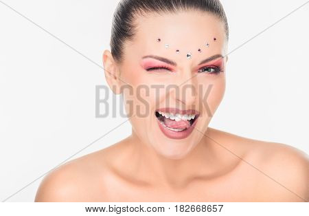 Pretty fashion woman with crystals on face showing tongue