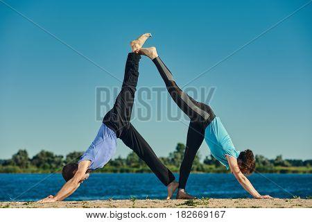 Man and woman practicing Eka Pada Adho Mukha Svanasana
