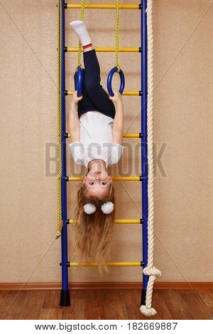 Little girl in sportswear hanging upside down on sporting rings on the wall bars. The concept of a healthy lifestyle from a young age. Children's sports.