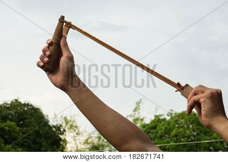 close up man use slingshot for insects and bird hunting in rural area
