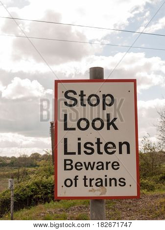 A Railway Safety Sign Saying Stop Look Listen Beware Of Train Red And White And Black And On A Pole