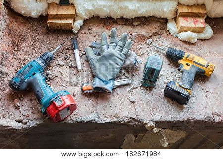 Some tools - drill screwdriver mounting knife mounting electronic level and worker's gloves are on the windowsill during under renovation remodeling and construction of apartment.
