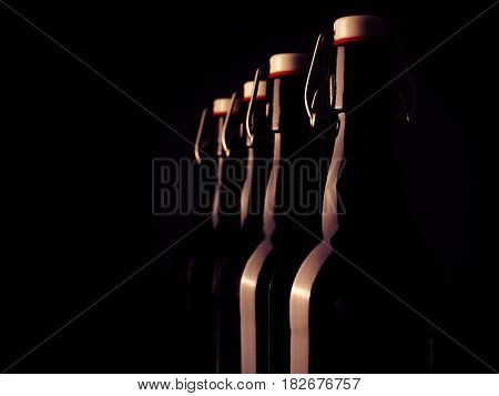 Four bottles of beer in a row on a dark background retro color toned