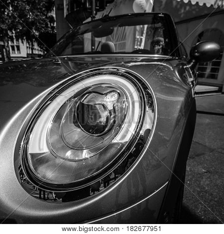 BERLIN - JUNE 05 2016: Headlamp of a city car Mini Cooper S Convertible. Black and white. Classic Days Berlin 2016.