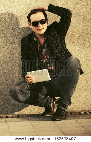 Young fashion business man with tablet computer sitting at the wall
