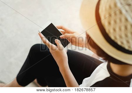 young woman holding a black screen of smart phone playing a social media sitting in a public park
