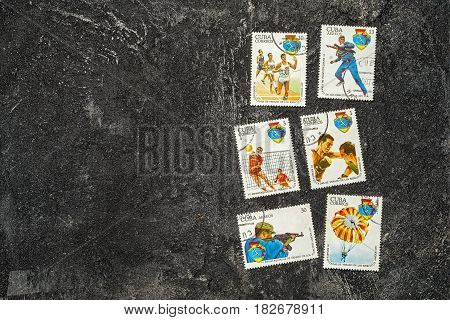 Moscow Russia - April 20 2017: set of randomly lying postage stamps printed in Cuba shows athletes and various sports devoted to 4 Spartakiad series circa 1977 on a dark black cement background