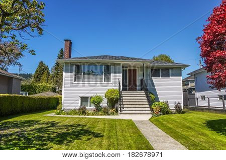 Old modest residential house with concrete pathway over front yard lawn. Family house with freshly mowed lawn on sunny day