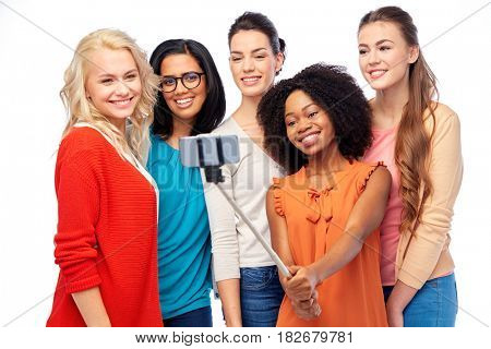 diversity, race, ethnicity, technology and people concept - international group of happy smiling different women over white taking picture with smartphone on selfie stick