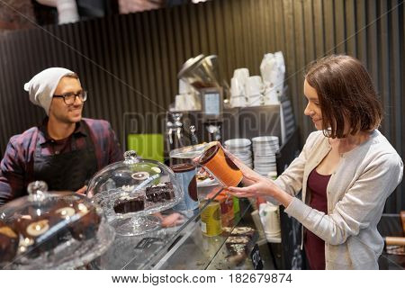small business, people and service concept - happy female customer buying chai latte instant drink and man or waiter at vegan cafe