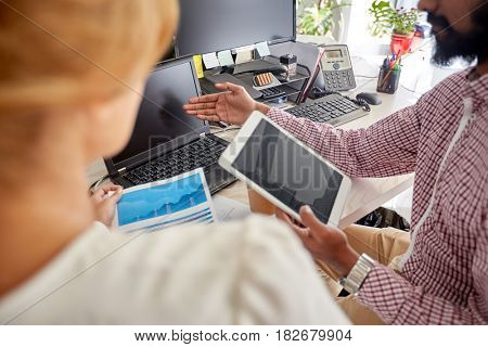 people, technology, statistics and corporate concept - business team with laptop, chart and tablet pc computer at office