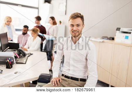 business, corporate, people and teamwork concept - happy young man over creative team in office