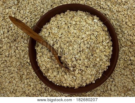 Dry oat flakes oatmeal in bowl on the background with wooden spoon