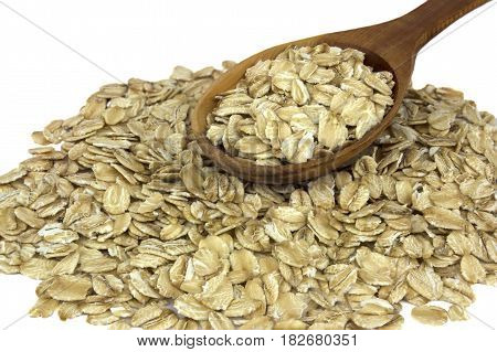Dry oat flakes on the white background with wooden spoon