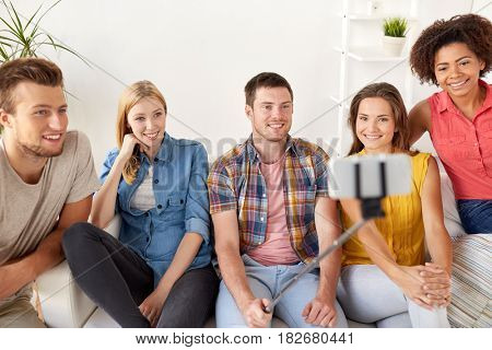 friendship, technology and people concept - group of happy friends taking picture with smartphone and selfie stick at home