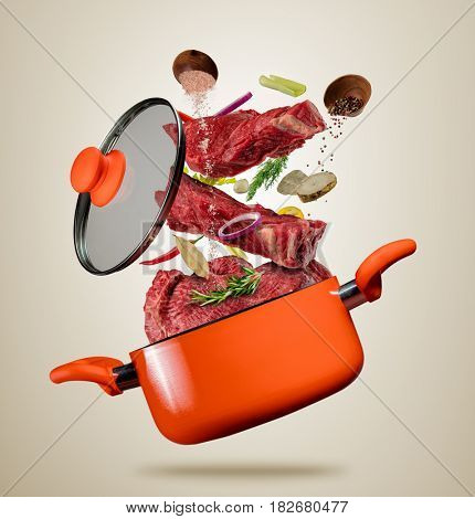 Fresh beef meat pieces with vegetable and cooking ingredients flying into a pot with lit, separated on gray background