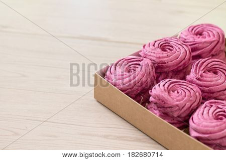 Currant zephyr or marshmallow in gift box on wooden background.